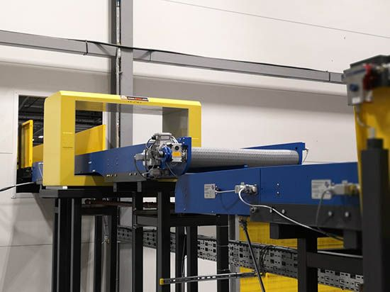 Plastics news conveyor system